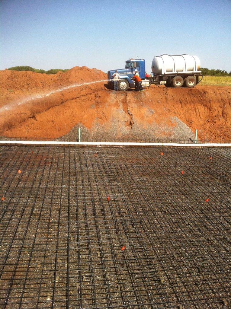 a construction worker spraying water to the reinforcement bars and cast before pouring concrete